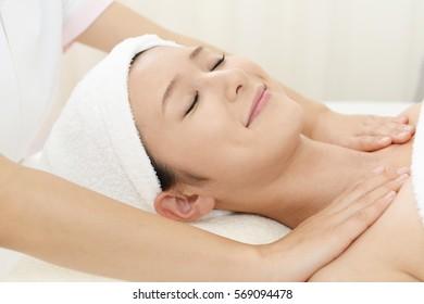 Woman receives body massage at spa salon