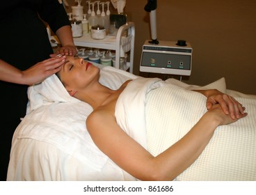 Woman receives facial massage at spa
