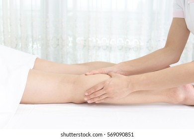 Woman receives leg massage at spa salon