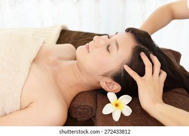 Woman receives massage at spa salon