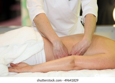 A woman receives a massage - you lies relaxed on a massage table.