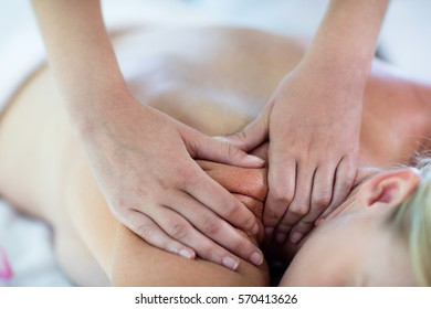 Woman receiving a back massage at spa