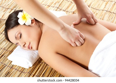 woman receiving back massage at spa salon