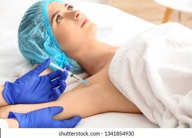 Woman receiving botox injection in armpit as treatment of hyperhidrosis in beauty salon