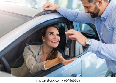 Woman receiving car keys from a dealer