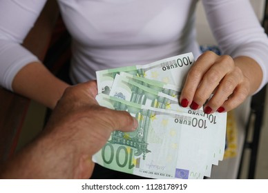 Woman receiving cash money from a man. Cropped image
