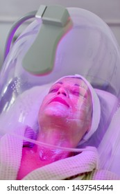 Woman receiving color light therapy for face. Facial therapy. Anti-aging procedures.
