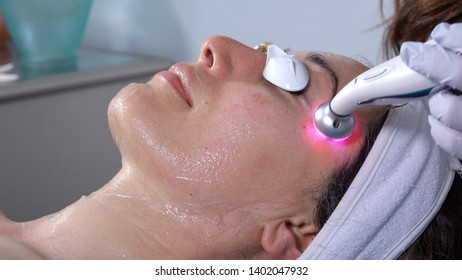 Woman receiving an eye lift facial treatment, using microcurrent LED technology, which promotes rejuvenation and tightens skin.