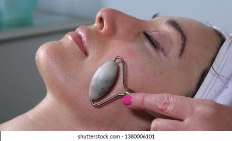 Woman receiving facial massage treatment with jade rollers