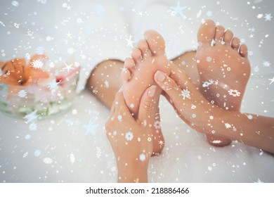 Woman receiving a foot massage against snow