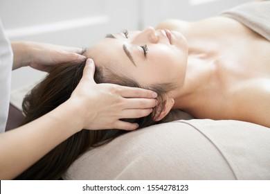 Woman receiving head massage in a bright beauty salon