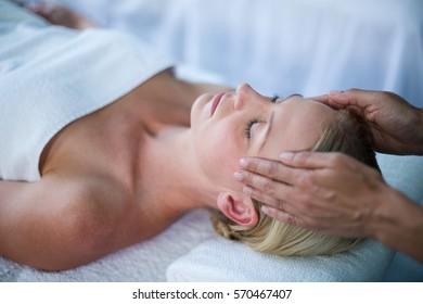 Woman receiving head massage from masseur in spa