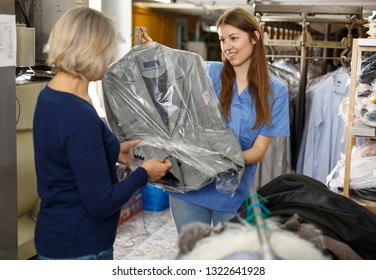 Woman receiving her clean menswear in plastic bags at dry-cleaning shop