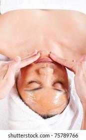 woman receiving honey facial massage at spa salon