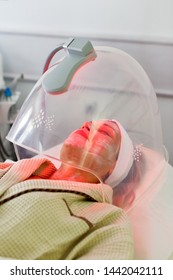 Woman receiving LED facial therapy for face.