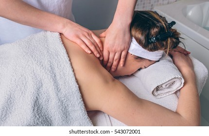 Woman receiving massage on neck in clinical center
