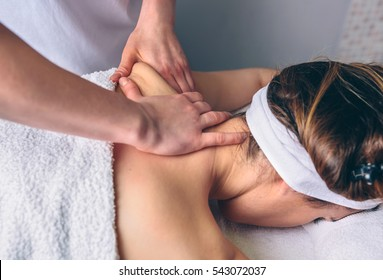 Woman receiving massage on shoulders in clinical center