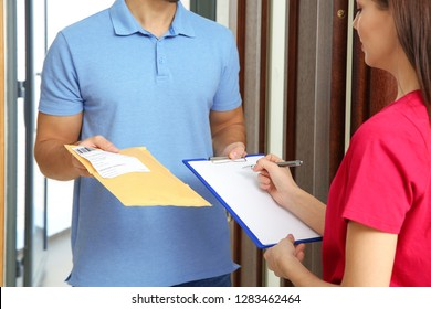 Woman receiving padded envelope from delivery service courier indoors, closeup