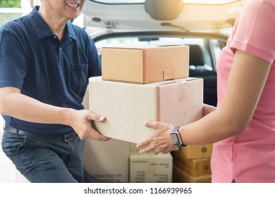 Woman receiving parcel cardboard box from delivery man Carrying Courier Shipping Mail from making an online order while standing in front of the house