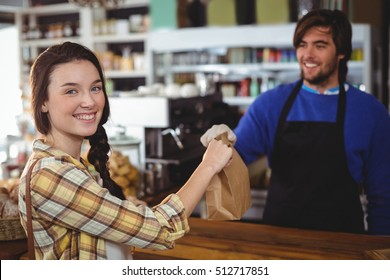 Woman receiving parcel from waiter at counter in cafe