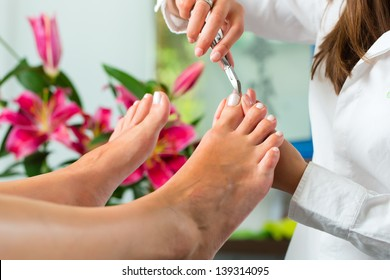 Woman receiving pedicure in a Day Spa, feet nails get cut and filed
