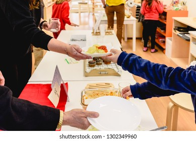 Woman receiving a plate of food from a child's hands at her school.