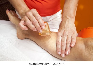 Woman receiving a professional anti cellulite massage with Ventuza vacuum body puller, while lying on a towel in a awarded health massage center,  series of HQ close-up photos