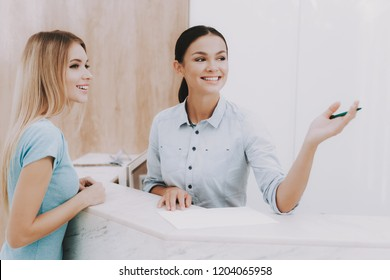 Woman Receptionist. Reception Workplace. Workplace in Beauty Salon. White Interior. White Reception Desk. Beauty Consept. Smiling Salon Employee. Customer Registration. Womans at White Reception.