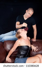 Woman reclining on a couch while her man sits above her, feeding her grapes by dangling them for her to bite