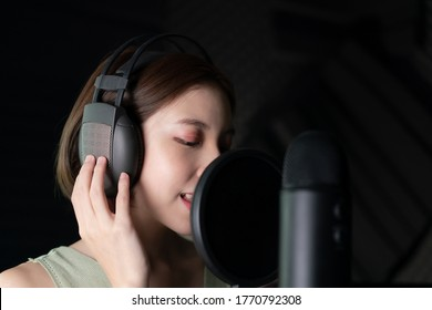 Woman recording a song or storytelling in the studio.