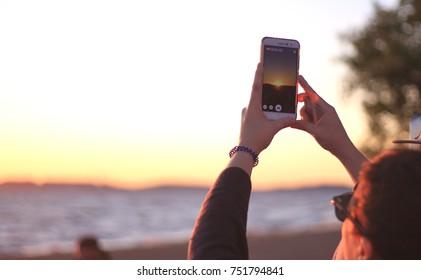 Woman recording the sunset over Guaiba Estuary. View from Ipanema Beach, Porto Alegre's South Zone