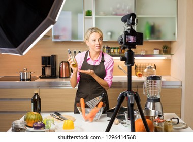 Woman recording video in her home kitchen, creating content for video blog