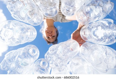 Woman recycling plastic water bottles high key looking up POV in New Zealand, NZ