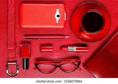 Woman red accessories with coffee, cosmetic, gadget and other luxury objects on leather background, fashion industry