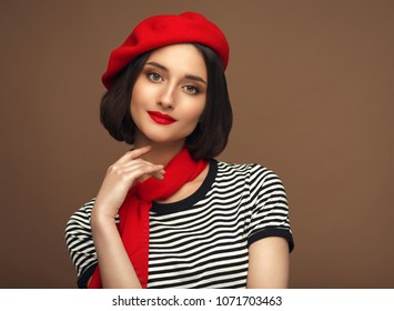 Woman in red beret and strippes T-shirt french style brunette with beautiful short hair over beige background