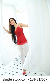 Woman in red blouse is posing near white curtains