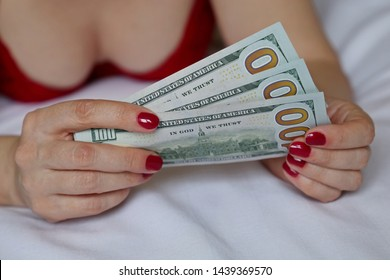 Woman in red bra lying in bed with US dollars in hands. Concept of savings, sex for money, prostitution, breast augmentation surgery