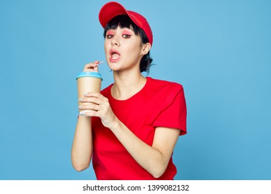 woman in a red cap holds a cof in her hand