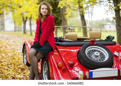 Woman in red and car at autumn park
