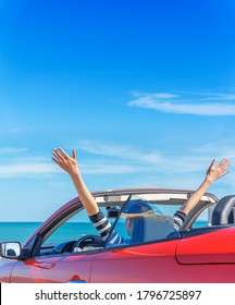 A woman in a red car raised her hands up at the seaside.
