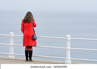 Woman with red coat with black boots sitting in front of sea. Young woman with red coat looking at winter landscape of frozen sea.