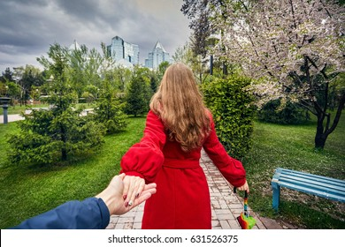 Woman in red coat and umbrella holding her friend and leading to the city park with cherry blossom and overcast sky