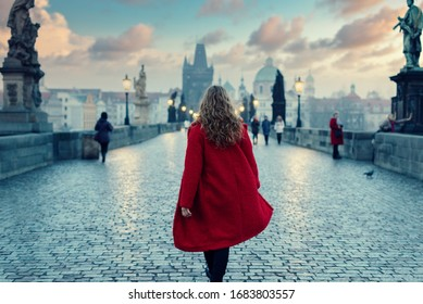 Woman in red coat walking on The Charles Bridge in Prague during the atmospheric sunset in winter