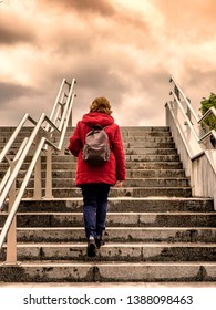woman with red coat walking up the stairs to the clouded  sky
