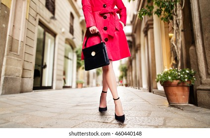 Woman with red coat,black handbag and shoes in the European town.