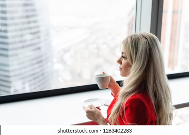 Woman in red coral business suit drinks coffee at a high table near the window. Young blonde businesswoman in the office in high floor in front of the window.