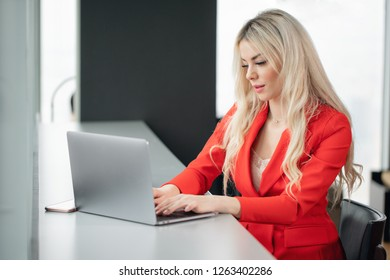 Woman in red coral business suit. Young blonde businesswoman with modern gray laptop in the office in high floor in front of the window. Girl drinking coffee