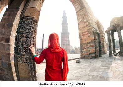 Woman in red costume looking at Qutub Minar tower in Delhi, India