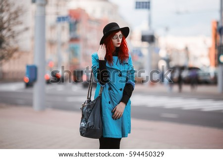 139034f9 Woman with red curly hair in blue coat and black round glasses on  background of big