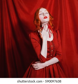 A woman with red curly hair in a dress and retro makeup on a red background. Red-haired girl with pale skin, blue eyes, a bright unusual appearance, red lips and ribbon around neck. Red magic